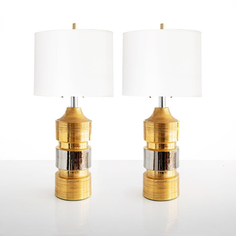 """Pair of ceramic gold and silver glazed lamps from Bitossi for Bergboms, Sweden. The lamps have been new polished nickel hardware, high quality Edison base sockets electrified for use in the USA.  Measures: Height 27"""" (adjustable), Diameter 6""""."""