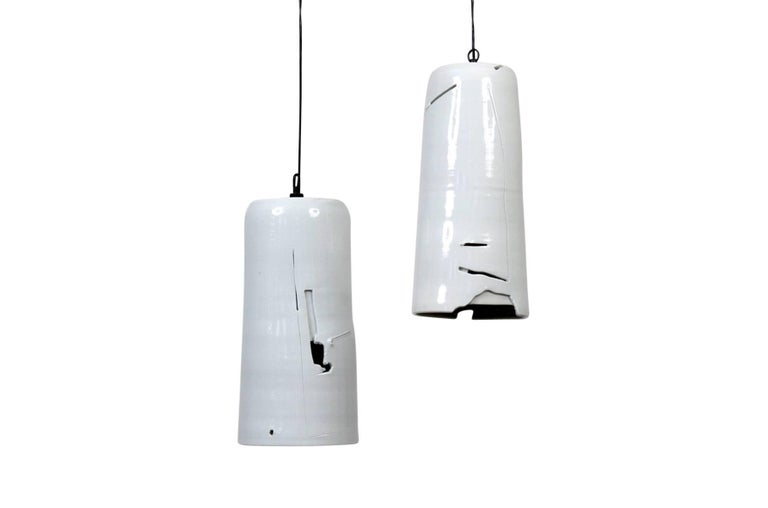 Pair of porcelain hanging pendants by ceramic artist Don Williams. Each cylindrical pendant with carved and sliced abstract decoration through which light escapes. Reminiscent of the Abstract Expressionist spirit of ceramicist Peter Voulkos' work.