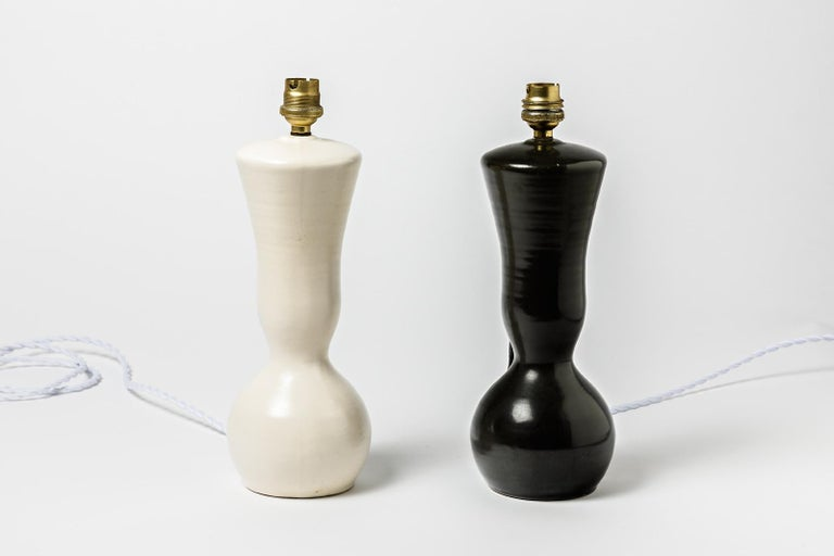Elegant pair of black and white ceramic table lamps.  Realized circa 1950 and attributed to Pol Chambost.  Original 20th century design  Original perfect conditions. Electric system is ok.  Sold without lampshade.  Price is for the