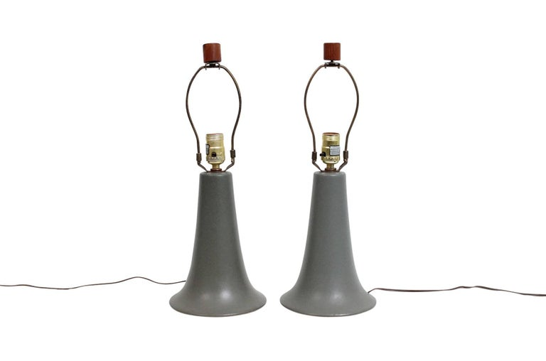 """Table lamps by Jane and Gordon Martz for Marshall Studios. Green matte glaze on bell shaped ceramic bases and iconic wooden finials. Both lamps signed. Dimensions below are for lamp with shade pictured. Dimensions of lamp body: Height 10"""", diameter"""