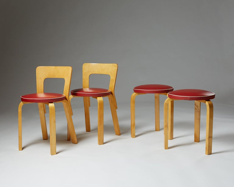 Pair of chairs and stools designed by Alvar Aalto for Artek, Finland, 1950s. Lacquered birch and red synthetic leather.