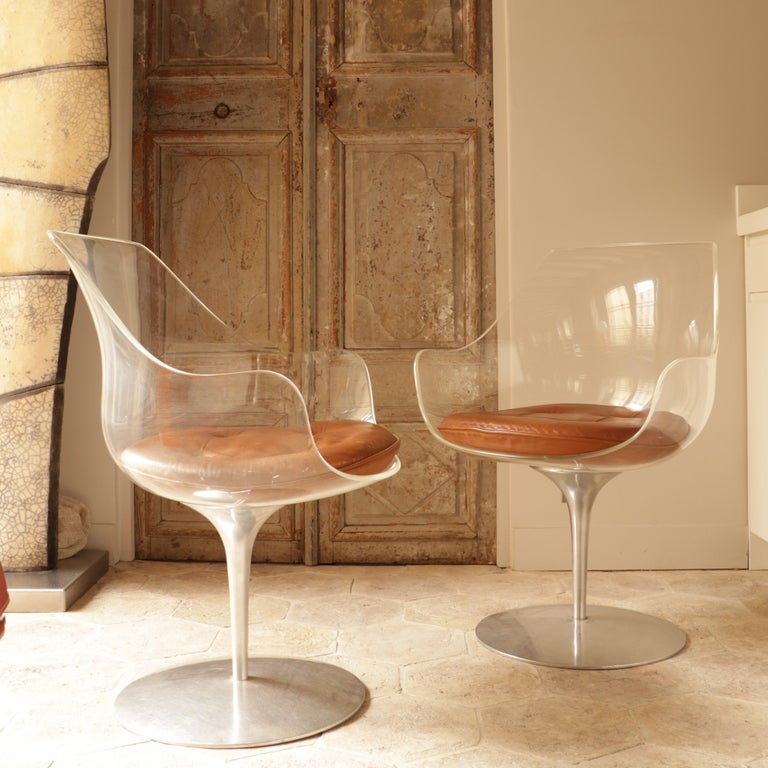 These two Champagne chairs are made of plexiglass and steel and have brown leather cushions. They were made by Estelle and Erwin Laverne in the 1960s. Erwine Laverne studied in the United States and then in Europe from 1928. In 1934, he met