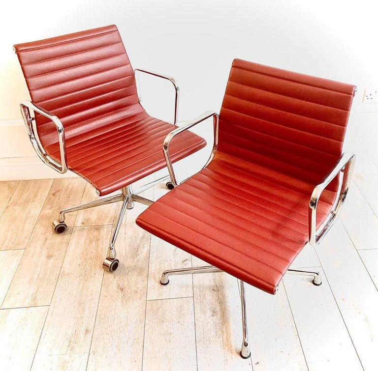 Great pair of Charles and Ray Eames Aluminium group office chairs in red leather made under licence by ICF, circa 2010.  Really used condition, very minimal signs of usage. One of the of the two chairs has castors and the other has glider feet