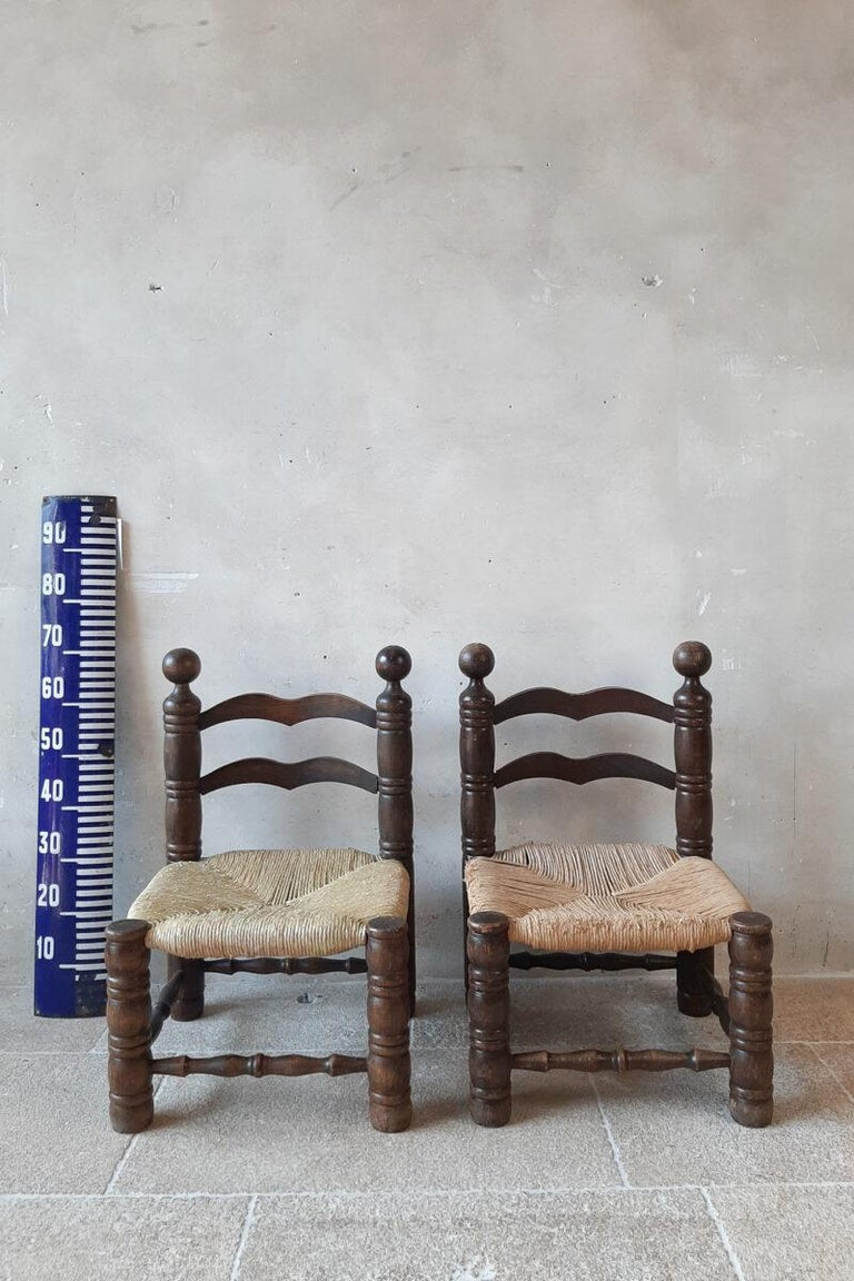 Pair of Finca style chairs by Charles Dudouyt. Small fire side chairs with beautiful carved oak frames and rationalist style wicker upholstery. Midcentury 1940s.   As you can see on the photos the wicker is a bit worn.  Measures: H 70 x W 46 x D