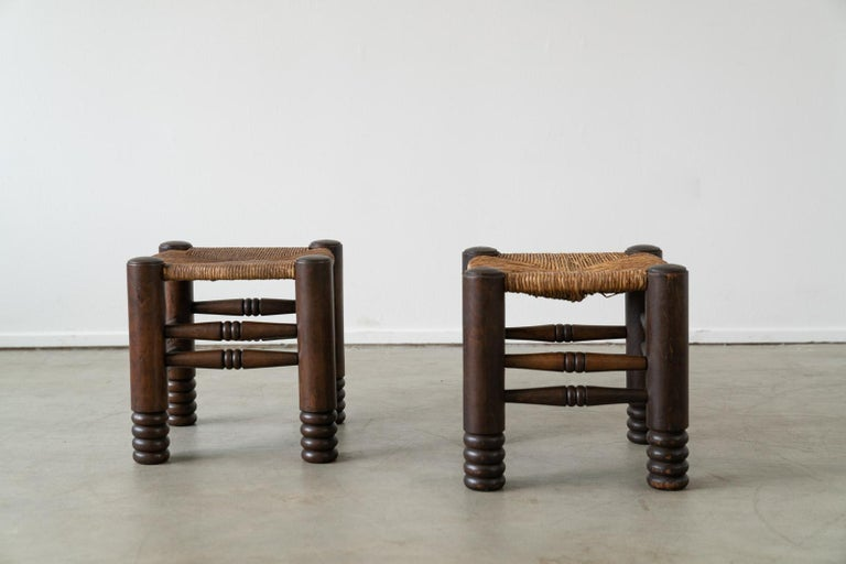Pair of Charles Dudouyt stool with signature carved legs and woven seat.  France, circa 1940's Great patina to seat.  Priced as a pair.