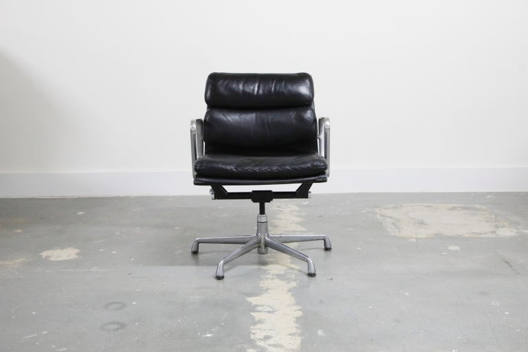 A collectible and sought after pair of leather 'Soft Pad' Management chairs from the Aluminum Group line, designed by Charles and Ray Eames for Herman Miller. Featuring its original black leather over five-star aluminum base. Signed underneath with