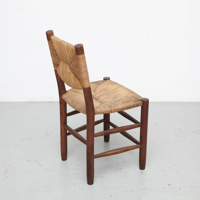 Pair of chairs designed by Charlotte Perriand, circa 1950. Manufactured in France.  Different editions of chairs made in wood base and legs with rush seat.  In good original condition, with minor wear consistent with age and use, preserving a