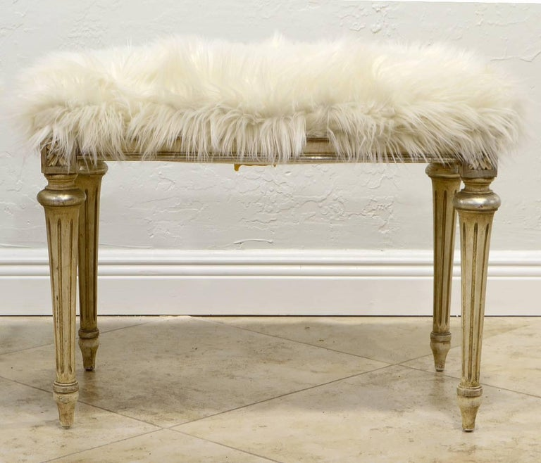 This pair of benches feature a white faux fur cover above a white painted and silver accented Louis XVI style frame with tapering fluted legs. They are retaining dated labels from Henry S. Berliner, New York.