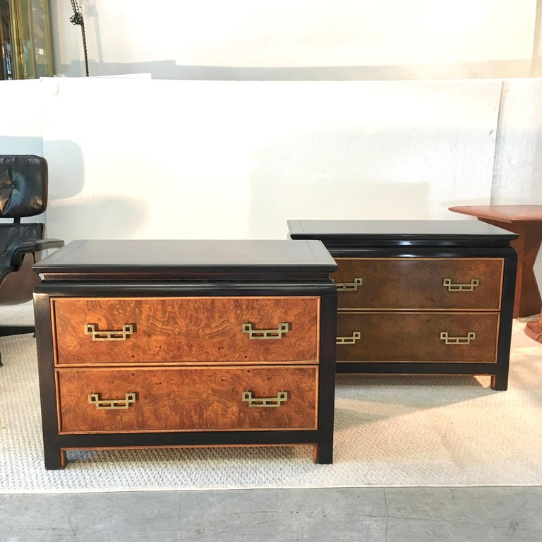 Pair of nightstands from the 1970s Chin Hua collection designed by Raymond Karl Sobota for Century Furniture. Two drawers with distinctive solid brass Asian inspired modernist pulls against burl wood drawer faces and sides on an ebonized case.
