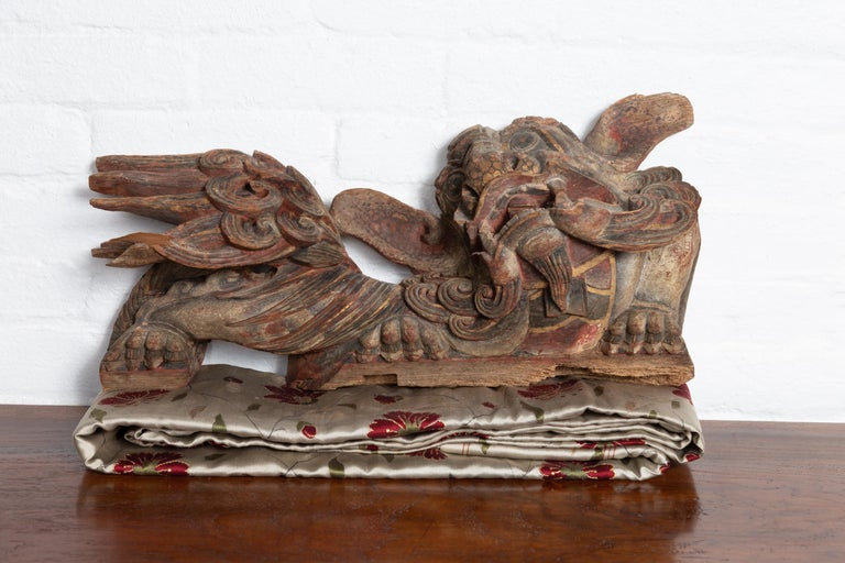 A pair of Chinese sculpted and polychromed temple guardian lions architectural wood carvings. Born in China during the 18th or 19th century, each of this pair of temple carvings depicts a hand carved guardian lion, facing left and right. Mesmerizing