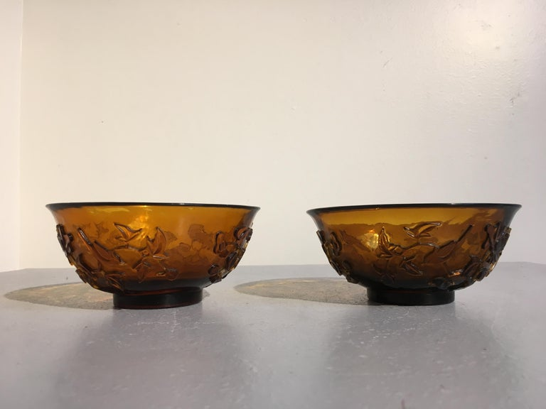 A fine pair of late 19th century Chinese Qing dynasty carved Peking glass bowls in a lovely amber hue.  The matching Peking glass bowls carved with opposing scenes of birds amongst flowering branches on a rocky outcrop. The amber glass bowls with
