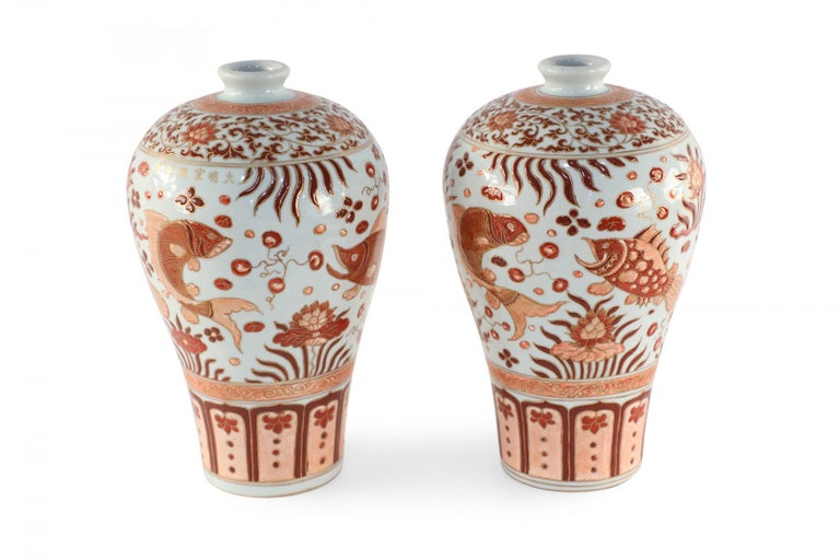 Pair of Chinese beige porcelain vases with Meiping forms decorated in orange fish and flower motifs and geometric-patterned bands around the tops and bases, accented in gold detailing.