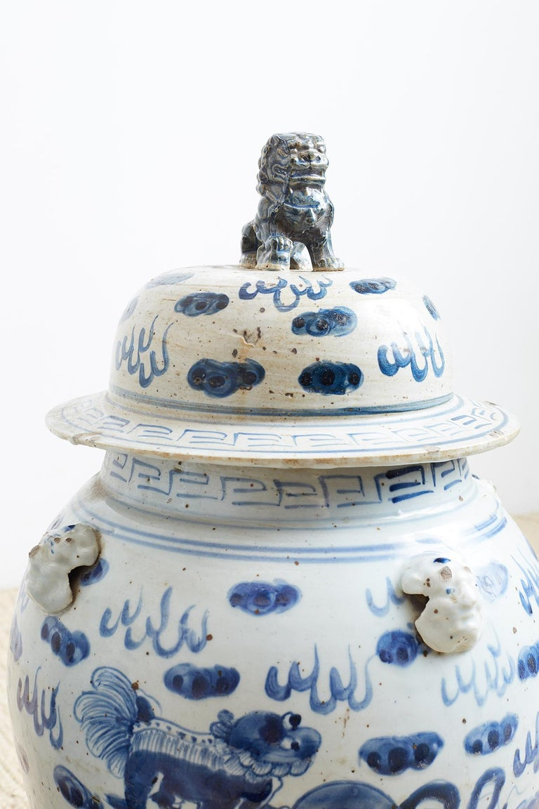 Large pair of Chinese blue and white ginger jars featuring painted foo dogs or lions amid whimsical clouds. Each jar has mythical beast heads on the shoulders. The matching lids appear to be original and have a large foo dog finial on top. Both have