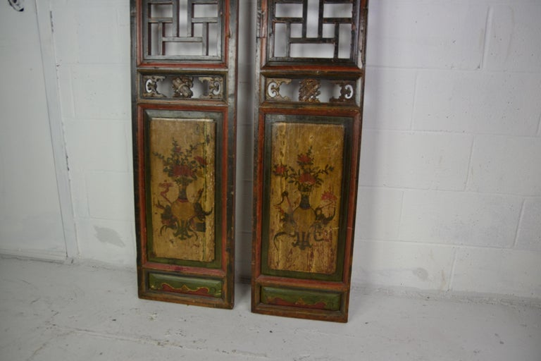 A pair of late 19th century Chinese panels in a red and black ground. Panels hand painted design over faded gold.