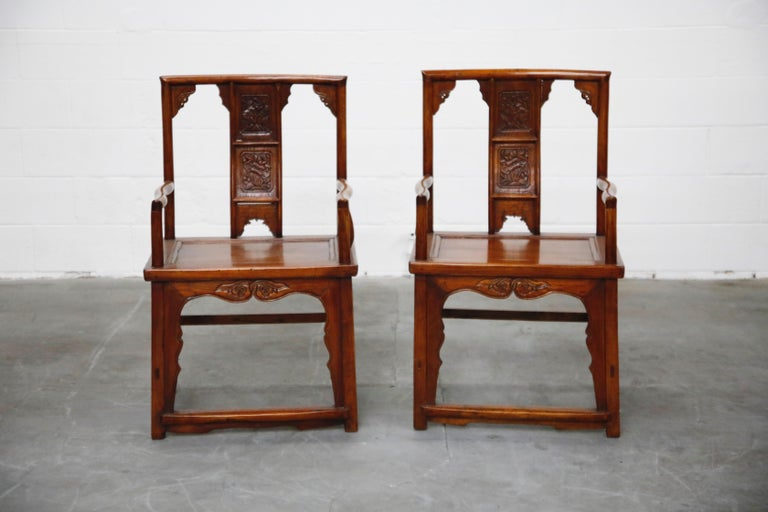 Pair of beautifully carved Chinese armchairs. These noble looking chairs have been expertly crafted, central splats which feature floral carvings that mirror one another. There are also etched embellishments of the seat back and rail. These