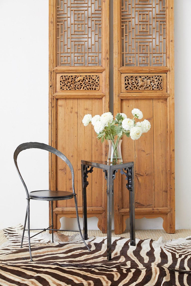 Distinctive pair of Chinese carved doors featuring an open fretwork design lattice panel windows. The thick frames have an old world mortise and tenon joinery. Standing over 9.5 feet tall and 20.5 inches wide. Decorated with foliate motif inserts on
