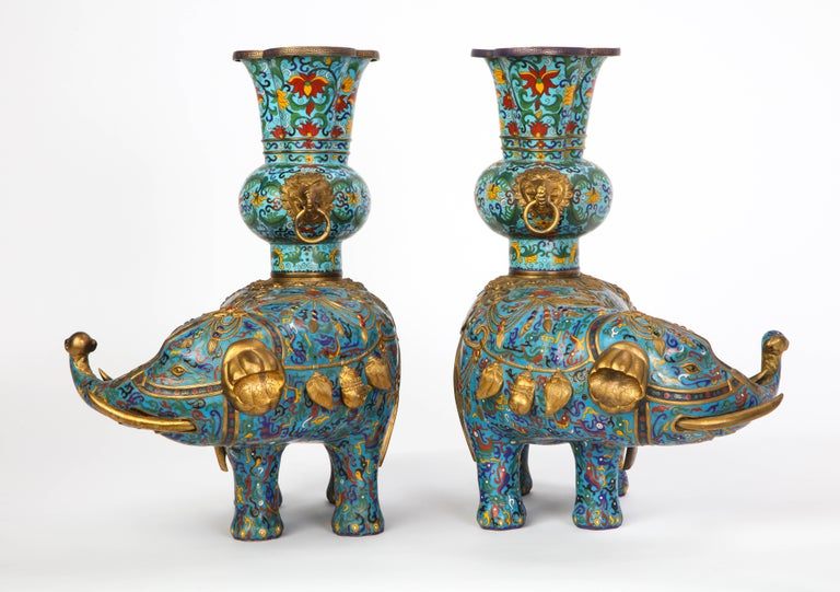 A pair of polychrome cloisonné enamel Chinese elephant-form pricket sticks, 20th century. Each with gilt-metal mounts. The red, green, blue, black and yellow scrolled foliate decoration is set against a turquoise blue ground.   Property from a