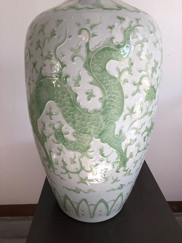 This pair of hand painted dragon vases are porcelain having a white background with pale green dragon design. Bulbous at top with small open rim. Large than normal.