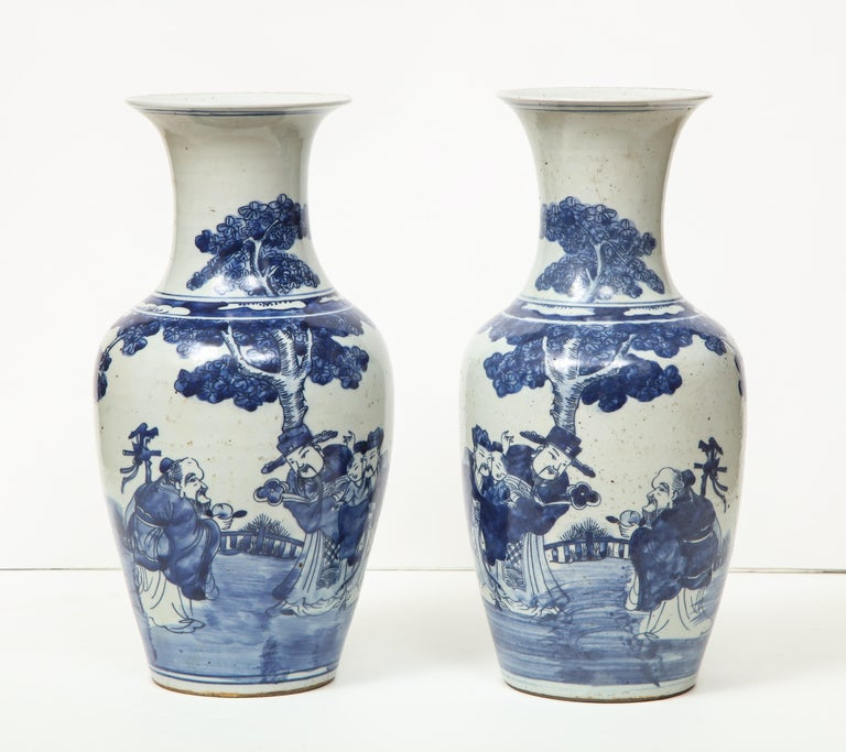 A pair of lovely Chinese export porcelain vases with a bottle neck. This pair have a timeless quality about them. They are the perfect accent pieces in a room and would look great on a mantle or as a centerpiece.