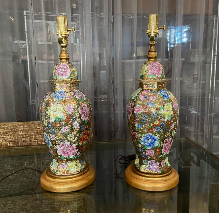 Pair of Chinese porcelain famille rose Millefleurs hexagon shape vases mounted as table lamps on giltwood turned bases. Beautifully crafted with bright applied floral images and 23k gold background accents. Newly wired including new brass fittings