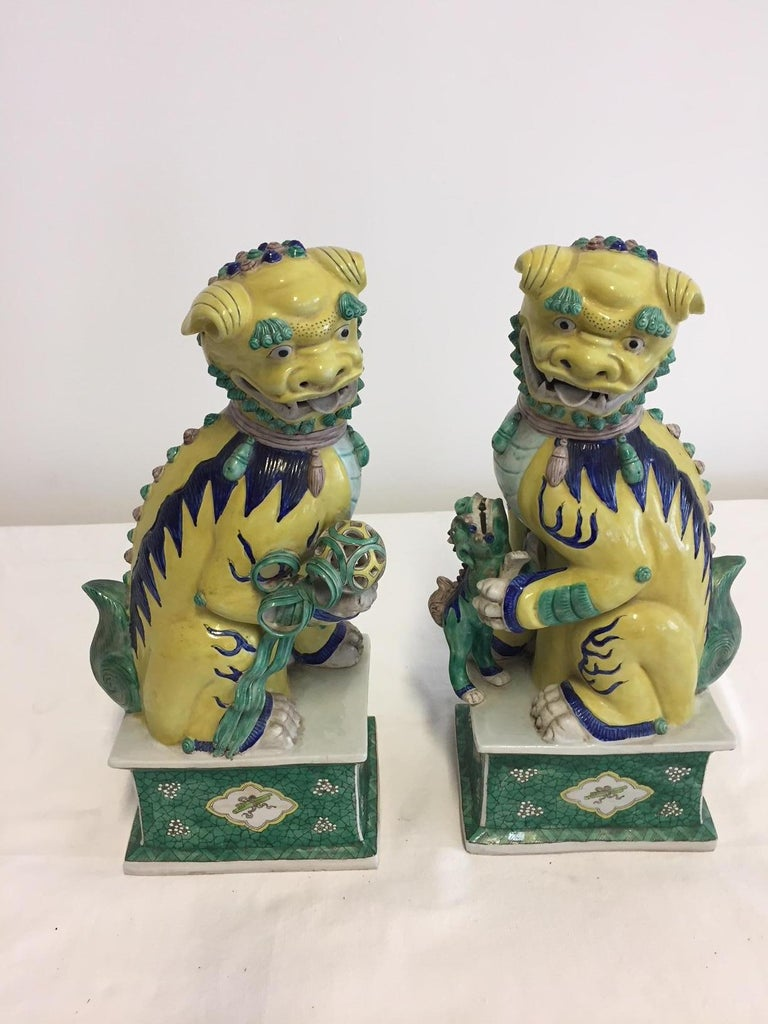 Pair of Chinese Foo dogs and painted stands, perfect condition, glazed hand painted porcelain in color yellow and celadon green and few high lights in color blue, beautiful details: male with ball, female with baby Foo dog.