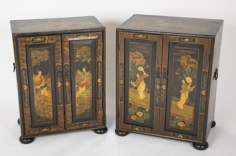 A near pair of Chinese Export chinoiserie decorated two-door low cabinets with interior shelves and drawers on bun feet.