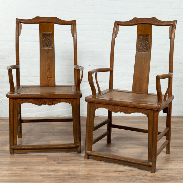 A pair of Chinese Ming Dynasty style elm scholar's chairs from the early 20th century, with unusual upper rail, carved panels on the splats, curved arms and rattan seats. Born in China during the early years of the 20th century, each of this pair of