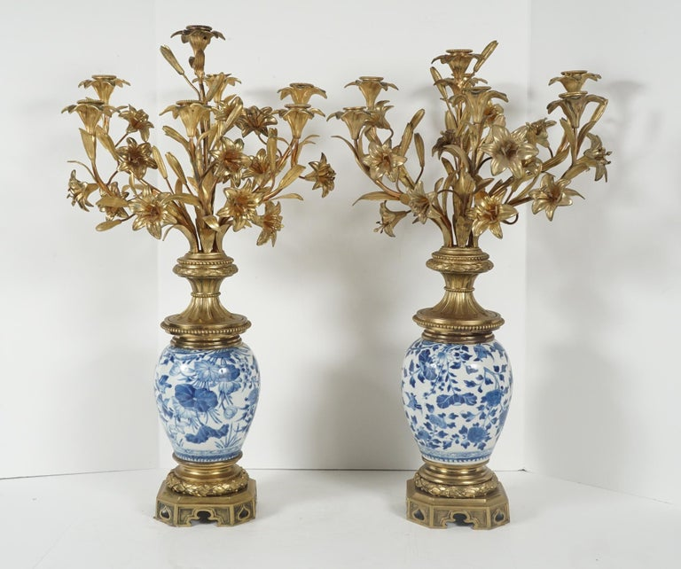 This pair of candelabra was made in France, circa 1850 and 1860. The porcelain is Chinese blue and white from the early 19th century. Beautifully hand painted the pair show water flowers and lily pads, reinterpreted in France and mounted as