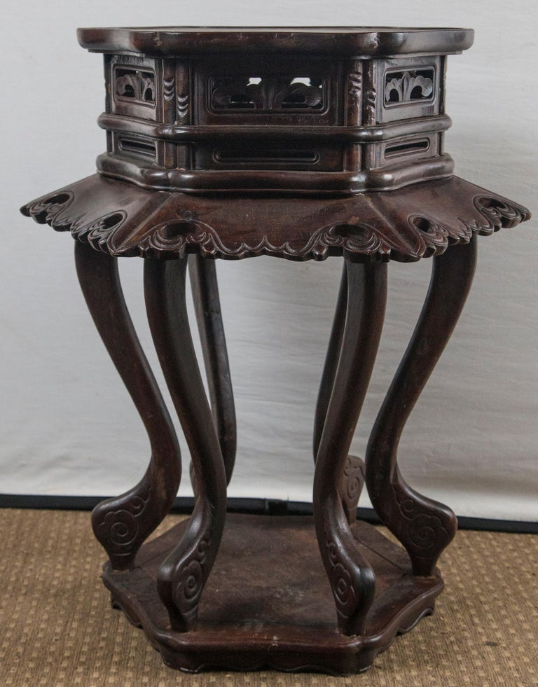 This pair have an unusual form. The 6 sided shaped top measures: 17.5 x 16 inches. Below is an open carved apron. A splayed out apron, also carved with openings, stands 4 inches out from the main body. Six in and out curving legs, sit atop a base