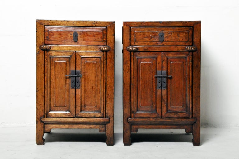 A restored pair of Chinese side chests. These chests are made from elmwood and were once covered in natural lacquer. That original lacquer (some oxblood remains) was gently removed and the wood grain was revealed and protected by a modern layer of