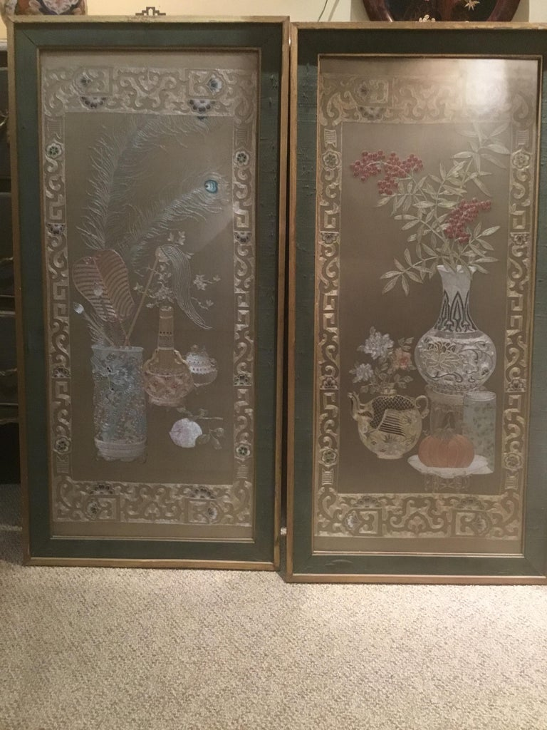 Handsome pair with intricate stitching. One depicting a vase of peacock feathers and the Other a vase of bamboo and a teapot, in giltwood frames, with opaque glass covering. Mounted on silk background. Exceptional stitching and exquisite use of