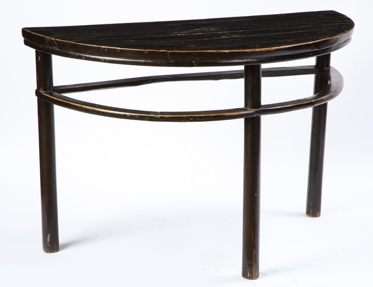 A pair of Chinese stained soft wood demilune side tables, 20th century. Demilune, French for 'half-moon,' tables often appear flanking a fireplace or in an entryway, where the flat back allows for the tables to sit flush on the wall while the curved