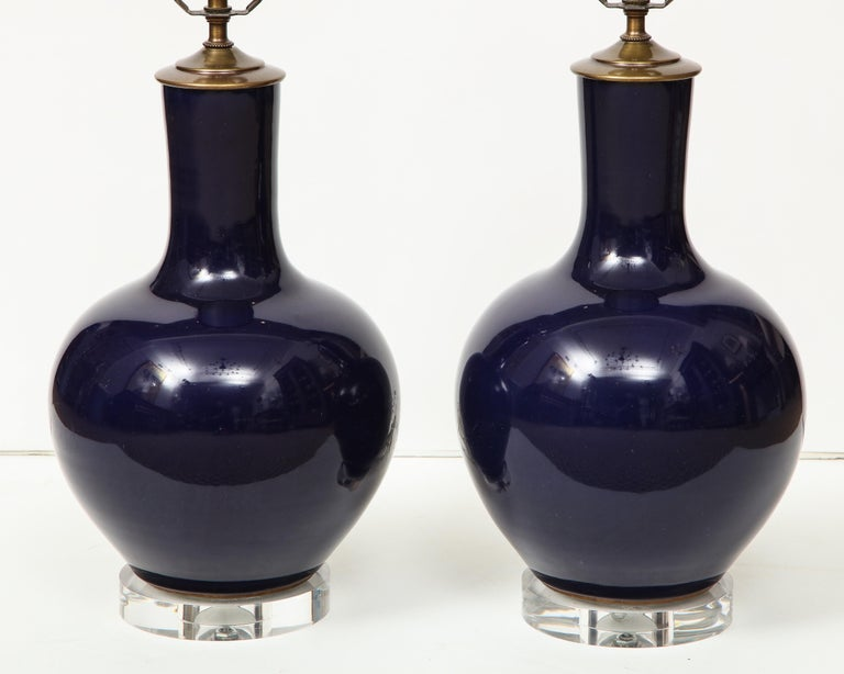 A pair of Chinese ceramic vase lamps in a deep navy blue on Lucite base.