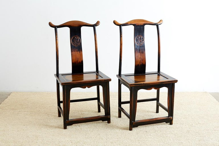 Dramatic pair of Chinese yoke back official's hat chairs featuring a Shuangxi emblem on the backsplat. These carved chairs have a lacquer finish with a distressed worn look and craquelure patina. Beautifully made with old world joinery and a smooth