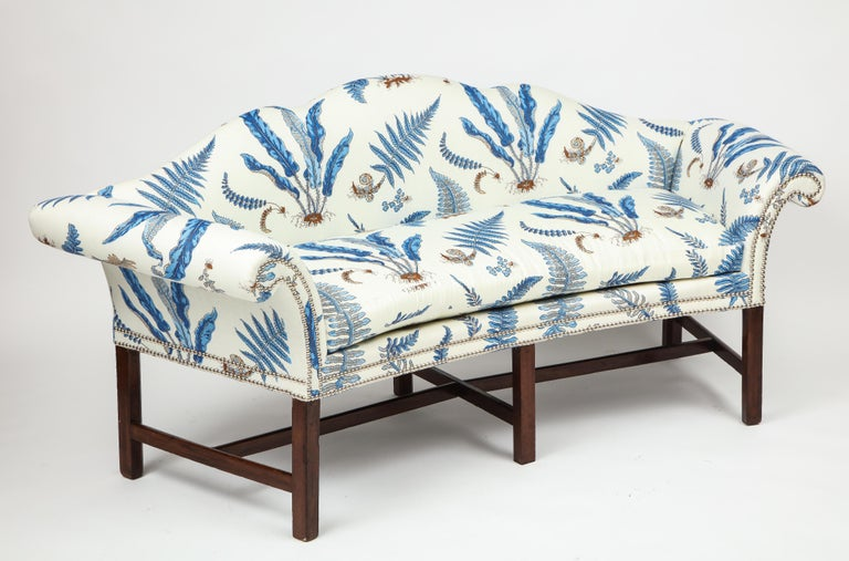 The serpentine back and outscrolled arms are particularly graceful as is the overall incurved form. On straight legs with H-form stretchers. Each newly upholstered in Bakers Ferns linen with silvered nailheads.