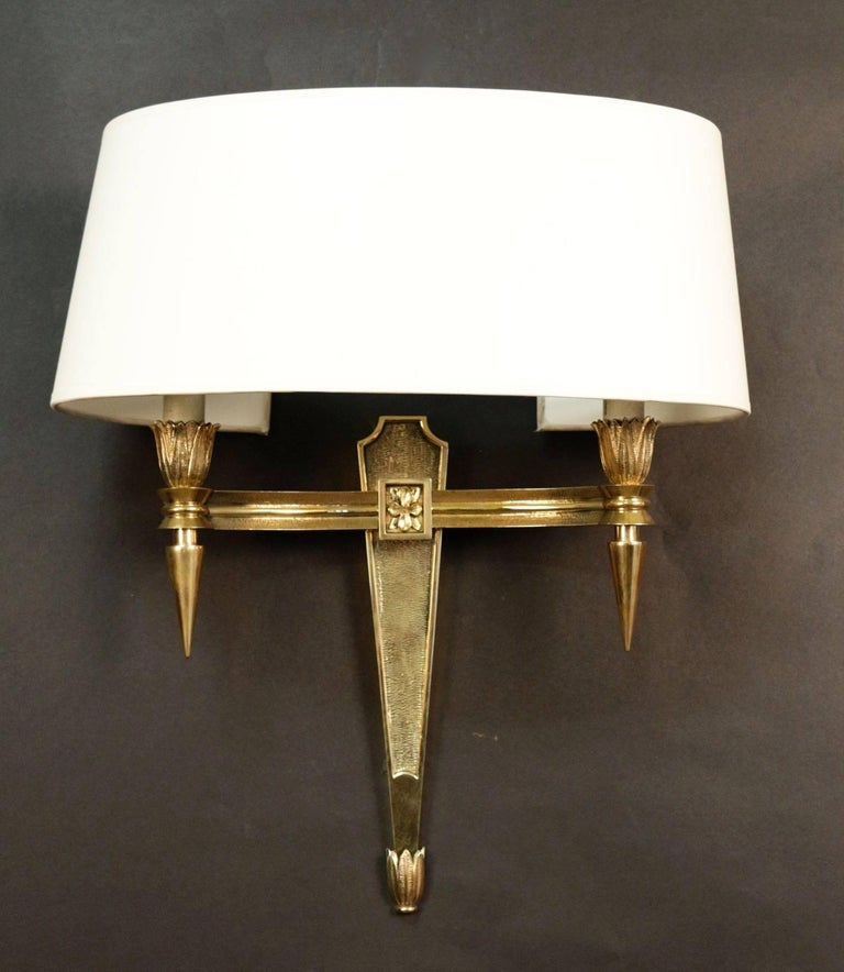 Pair of 1950s neoclassical sconces in chiseled bronze. They consist of two lighted arms with sockets endings supporting bulbs. French work. Probably by Maison Jansen. New lampshade redone according to the original. Perfect condition.