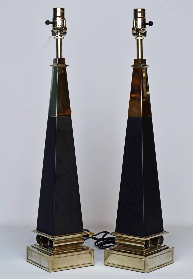 These Mid-Century Modern table lamps in the shape of obelisks represent an iconic Tommi Parzinger design. They feature chrome top sections above ebonized wood columns resting on a square chrome base intersected by classical inspired chrome cylinders.