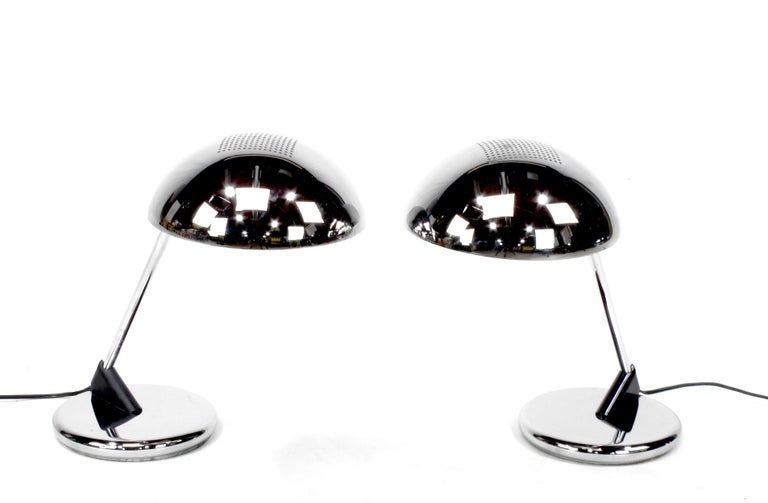Uncommon pair of chromed steel desk lamps with cantilever dome shade and weighted base, circa 1960s, these are the only pair we have been able to find. They could possibly be Italian or German. Either way they are a fantastic looking pair of desk