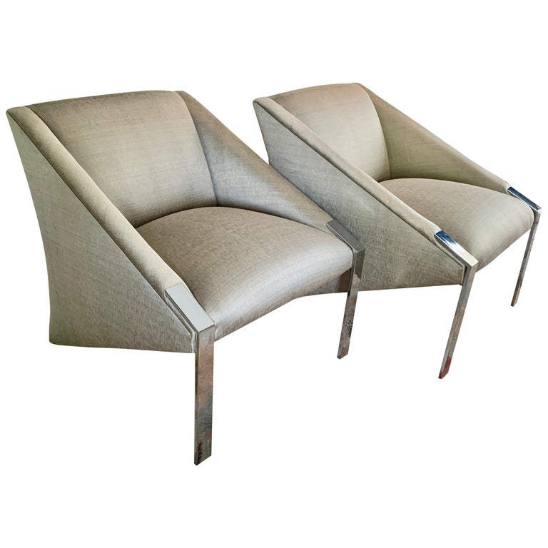 Pair of chrome side / lounge chairs by Iconic French Designer Andree Putman - the pair rest on high polished chrome legs and slant back to meet the ground. The pair are reupholstered in a very chic neutral woven silk fabric - wonderful for any room.