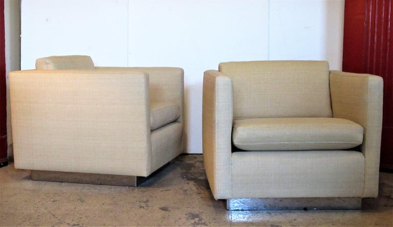 Pair of big chrome clad platform base cube lounge chairs having a floating form and a very tailored sophisticated look. The chairs were upholstered within the past ten years in a beautiful commercial grade natural straw colored textured grass cloth