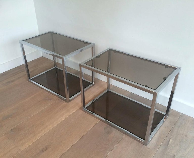 This pair of side tables are made of chrome with smoked glass shelves. This is a French work, circa 1970.
