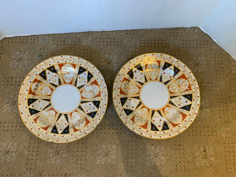 Pair of 19th century circa 1810 English Coalport round porcelain plates with elaborate gilt detailing and old sticker.