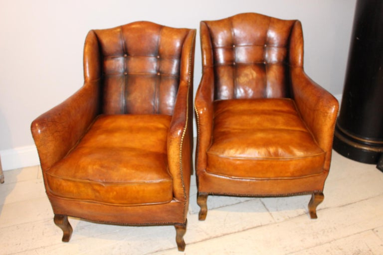 A Classic pair of stylish Swedish leather studded armchairs. The leather is original apart from the cushions which have been replaced and color coordinated to carefully match the rest of the armchairs. The leather has a soothing warm, mid-tan color,