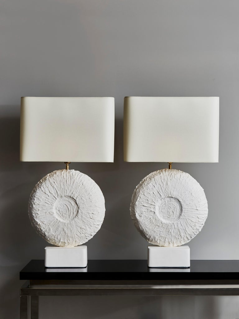 Pair of beautiful table lamps made of a round textured plaster centerpiece and feet with brass settings.  Contemporary work made in France.