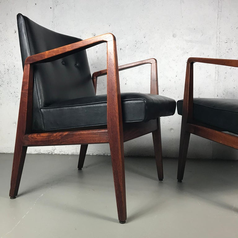 Beautiful pair of occasional or lounge chairs in walnut and black vinyl designed by Jens Risom for Jens Risom Designs. These chairs are in original condition and the walnut has wonderful dark swirling grain. These chairs have patina that present