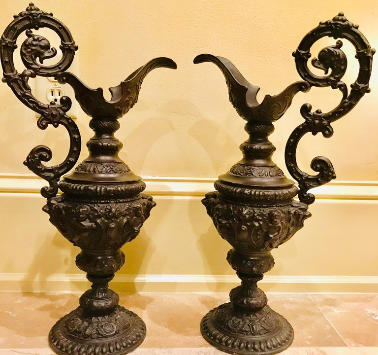 In the Renaissance style, a pair of cast, oiled bronze fountain ewers were originally mounted with piping, pouring perpetually into a basin in a garden in Holland.   These classical ewers are detailed with cherubs, vines and other classical