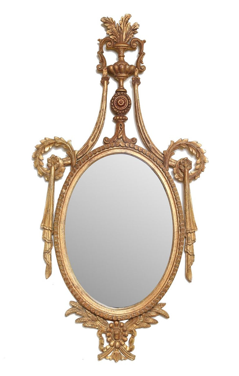 Pair of mirrors, in richly carved giltwood frame, each having an oval mirrorplate, with border of gadrooning, surmounted by elaborate pediment of acanthus-filled urn, over rosette, flanked by swags and scrolls, its base adorned by wheat, ribbons,