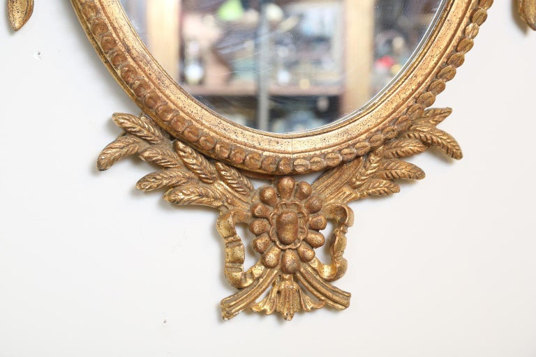 Hand-Carved Pair of Classical-form Italian Carved Giltwood Oval Mirrors For Sale