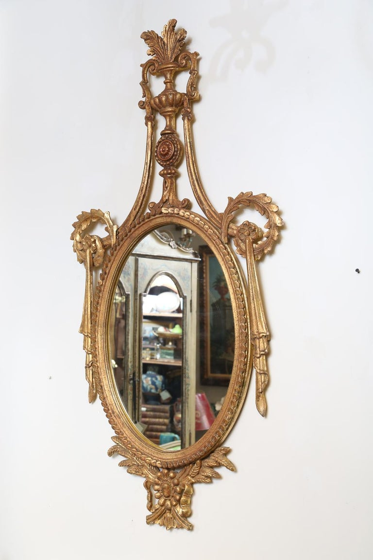Mid-20th Century Pair of Classical-form Italian Carved Giltwood Oval Mirrors For Sale