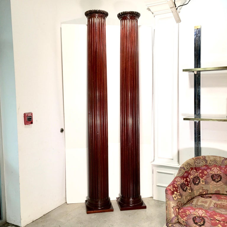 Pair of antique architectural round fluted columns made entirely of solid mahogany, on square base and carved egg and dart capitals. Twenty four flutes as per Vitruvius! Measures: 100 inches tall, 11 inches diameter at entasis, base is 13-5/8 inches